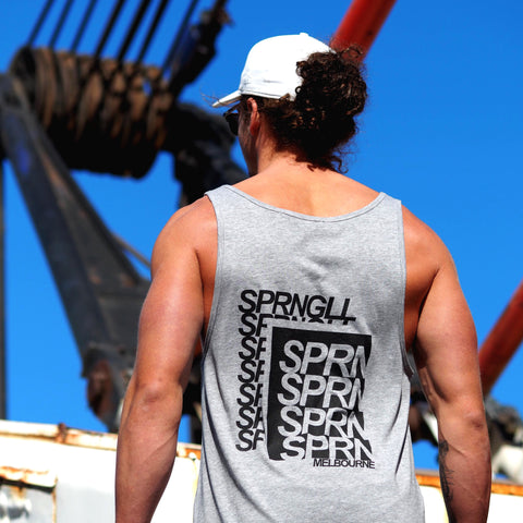 Man wearing a grey singlet with SPRNGLL printed on the back facing away