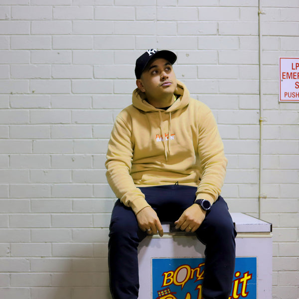 Man sitting on a freezer looking up with a tan hoodie and black joggers on