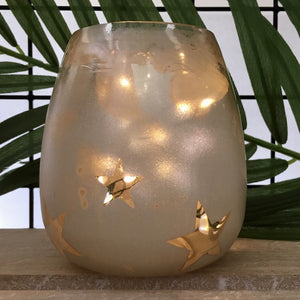 Glass tea light holder or vase in champagne colour with scattered star stencils