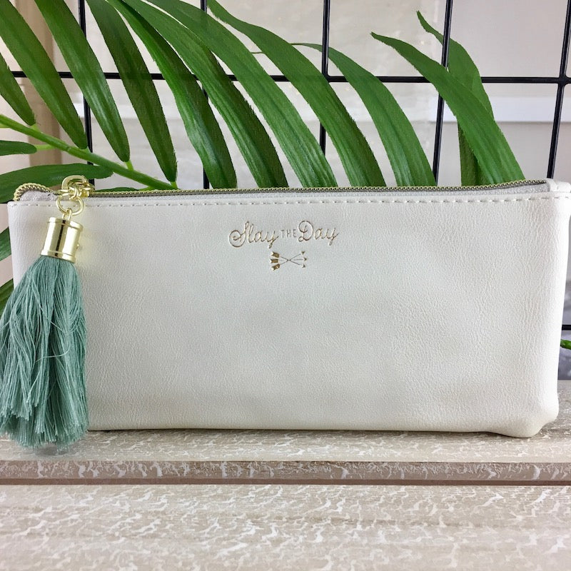 Ivory pouch with teal tassel and 'slay the day' gold lettering