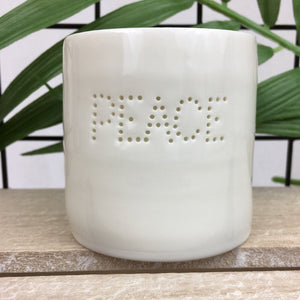 Ivory porcelain tea light holder with pinhole word peace design