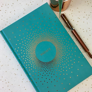 Teal coloured hardback notebook with copper foil dots and the word 'radiate' on the front
