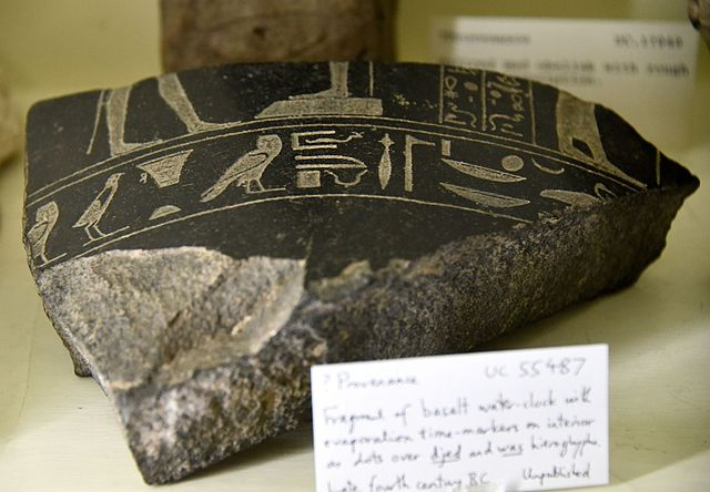 Fragment of a basalt water-clock, with evaporation time markers on interior as dots on djed and was hieroglyphs