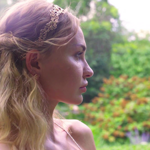 Model is wearing Flower headband paired with Origin Stud earring in rose-gold tined blush silver