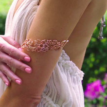 Model is wearing Flower arm cuff in rose gold toned blush silver