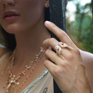 Model is wearing Adjustable Angel Wing Ring in rose-gold toned blush silver