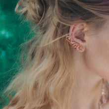 The model is wearing Baby B Climber Earrings with stud backs in rose gold toned blush silver