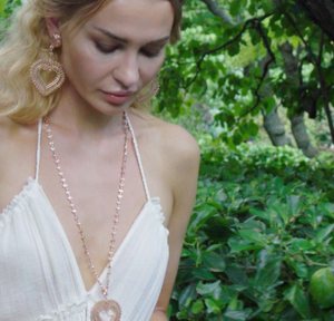 Model is wearing Heart Long chain necklace paired with Heart Medallion in rose-gold toned blush silver