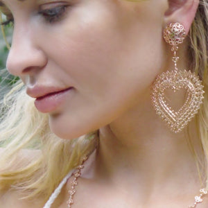 Model is wearing Heart Statement earrings in rose-gold toned blush silver