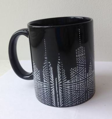 A Museum of the City of New York black ceramic mug with handle. The mug has a white graphic of the stunning Starlight installation which is like a geometric matrix-like cityscape at the bottom of the mug.