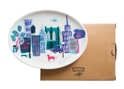 A white ceramic tray with colorful graphic depictions of iconic New York City landmarks in the shades of blue, orange, and pink. Coordinates with Collage City mug and bowl by Beatriz Gutierrez.