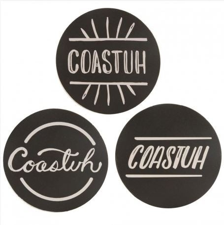 "Black cardboard coasters with white lettering spelling ""Coastuh"". Four of each of three different designs for a total of twelve coasters in the set."