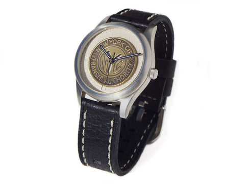 A wristwatch with a thick black leather wrist strap and a bronze NYC subway token as the face.