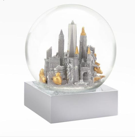 Clear Glass Snowglobe with silver base. Inside is a selection of famous NYC landmarks rendered in silver and gold.