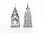 Whimsical, detailed silver-toned salt and pepper shakers that depict The Empire State Building and The Chrysler Building.