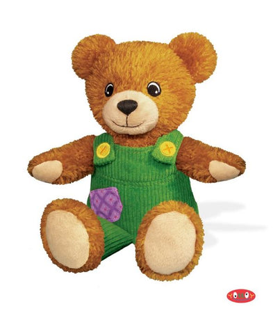 A corduroy the bear plush stuffed animal with green corduroy overalls and a purple patch.