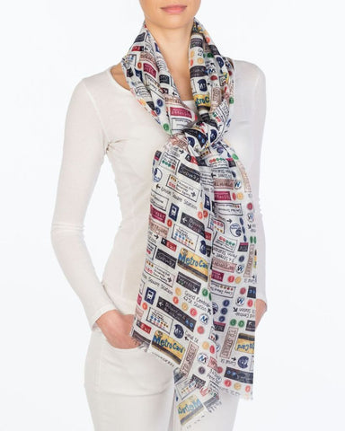 A white scarf with train symbols in various colors. Symbols include: metro card, light rail, subway signs, etc.