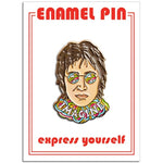 A one inch enamel pin in the shape of an illustrated portrait of John Lennon.