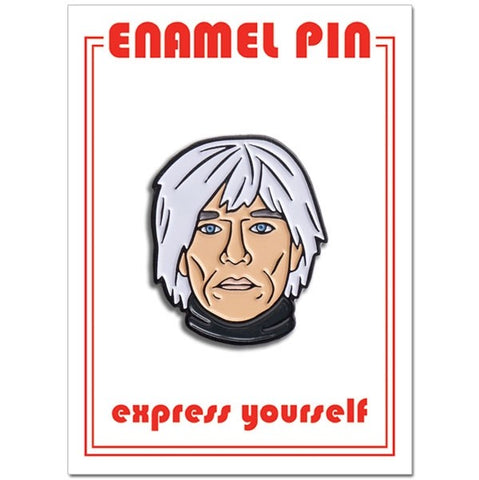 A one inch enamel pin in the shape of an illustrated portrait of Andy Warhol.