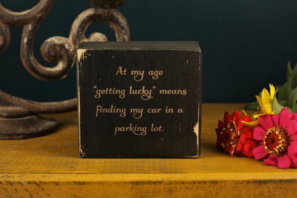 "Funny decor block with the saying ""At my age ""getting lucky"" means finding my car in a parking lot."""