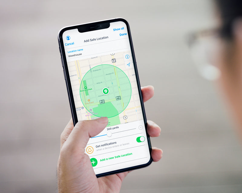 person holding smartphone showing add safe location feature