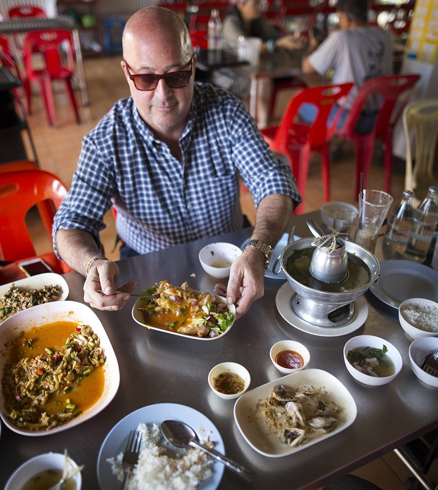 Andrew Zimmern digging into his food in Bangkok