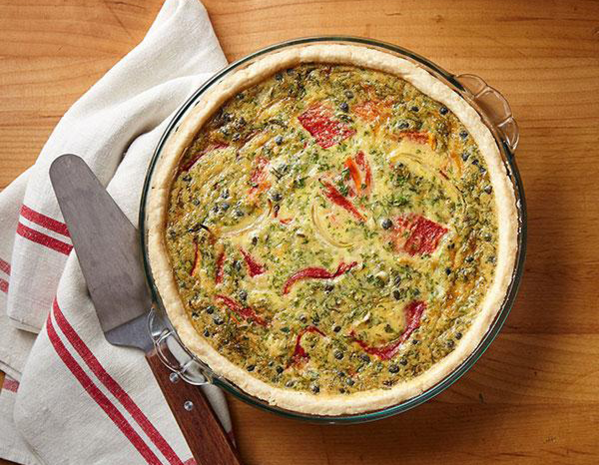 Quiche baking in an old fashioned pyrex glass pie dish