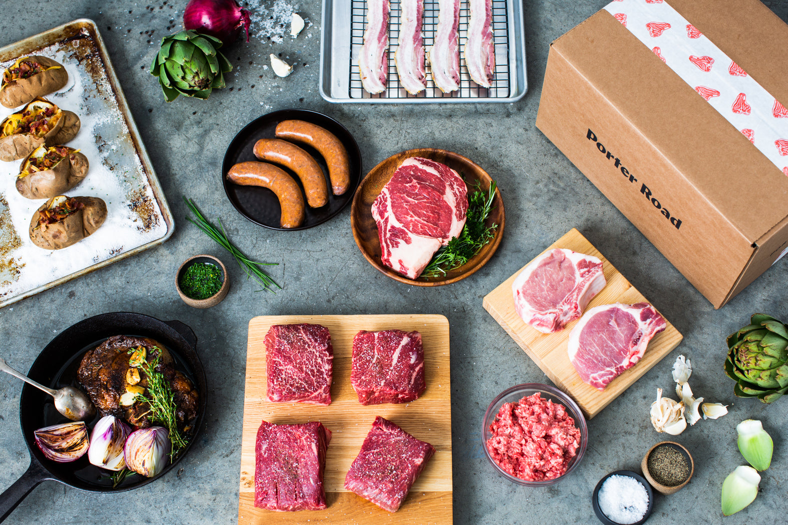 Porter Road meat subscription box shown with a display of steak, sausage, bacon, baked potatoes, and other ingredients.