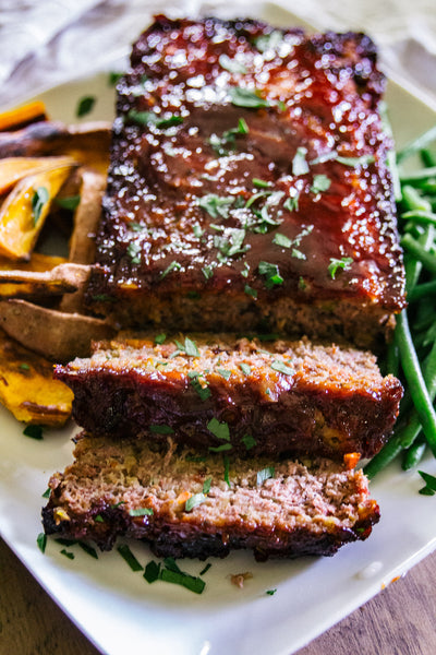 Sliced meatloaf with sweet potatoes and green beans.