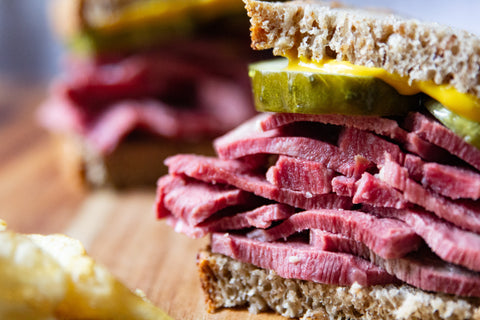 Beef tongue corned beef sandwich with pickle slices and mustard