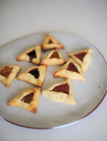 Jam-filled Hamantaschen on a plate by Issa Pottery