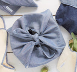 Heirloom Wrap in Chambray carries a pie. You can see the bow that forms a tie to carry the dish.
