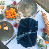 Heirloom Wrap in Large in Denim by Millie Lottie carries a casserole dish, placed on a picnic table for a potluck