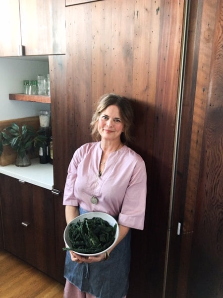 Jan of Millie Lottie leaning against a wall holding a bowl of Kale for her seriesm KALE THREE WAYS