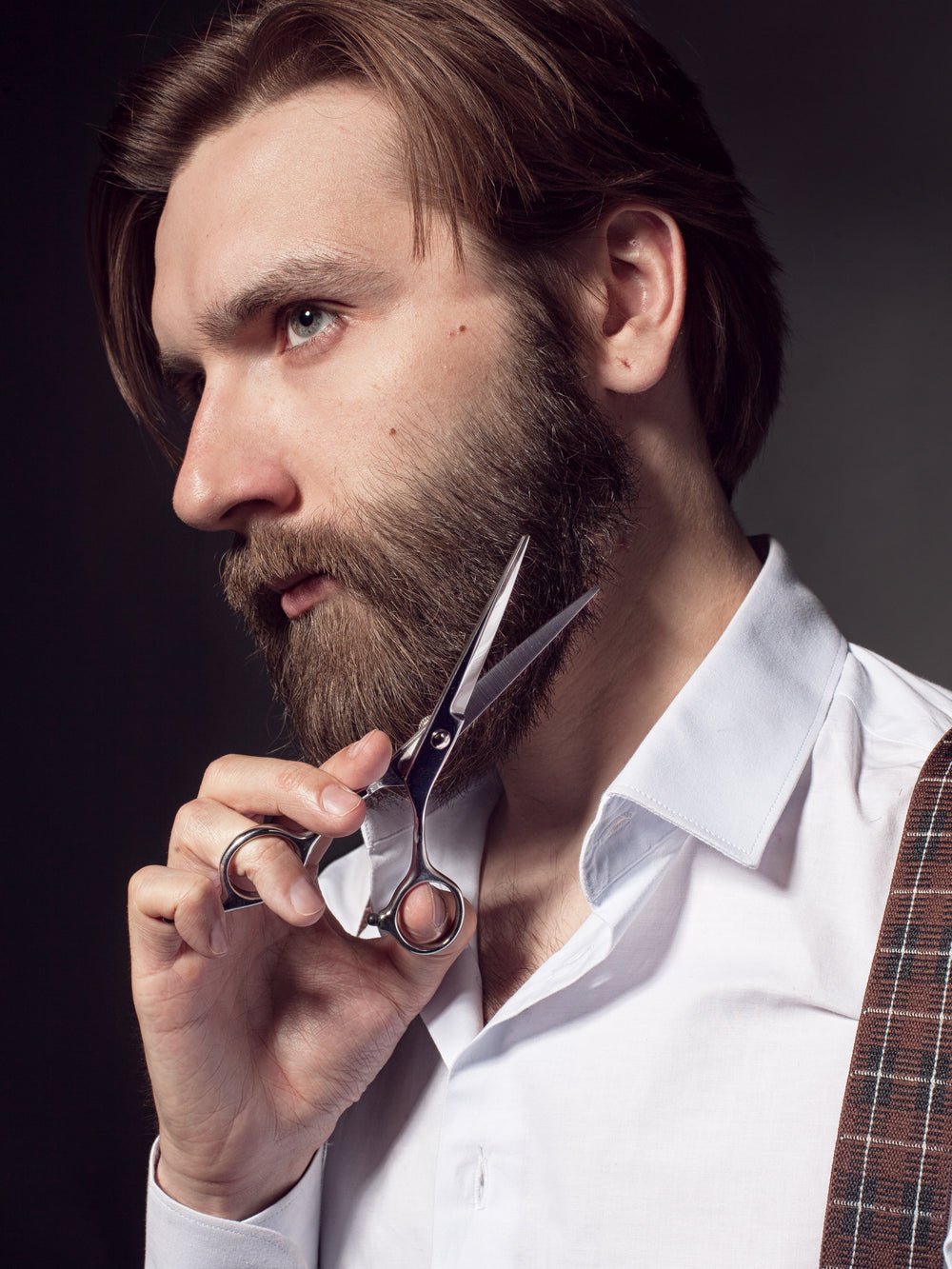 Dark haired bearded man using Beard Reverence scissors to trim his beard.