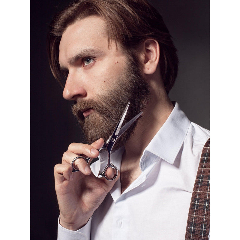 Dark haired bearded man in a white shirt trimming his beard with Beard Reverence Barber-Grade Scissors.