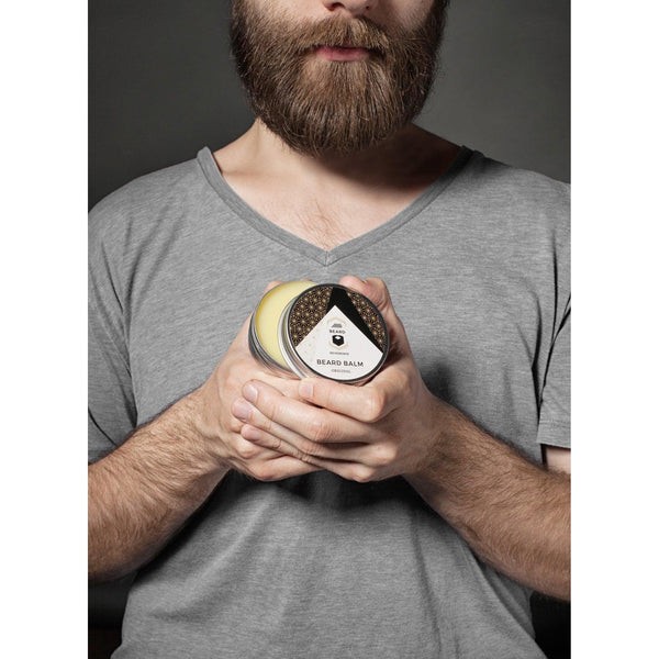 Bearded man in a gray shirt holding up a an open container of beard balm by Beard Reverence