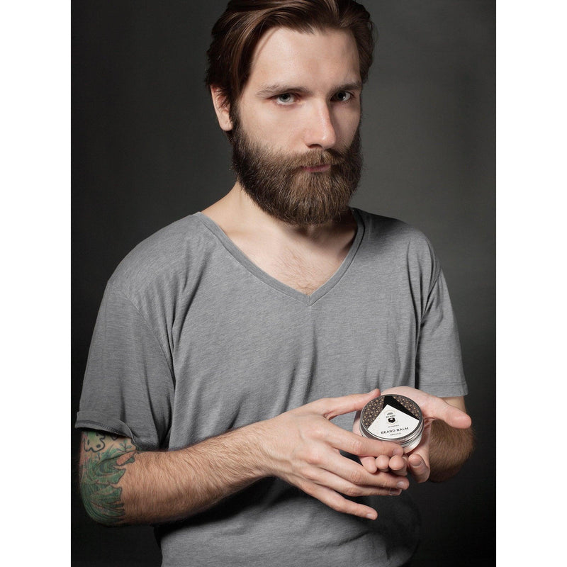 Man with a beard, tattoo, and dark hair, holding a tin of Beard Reverence beard balm.