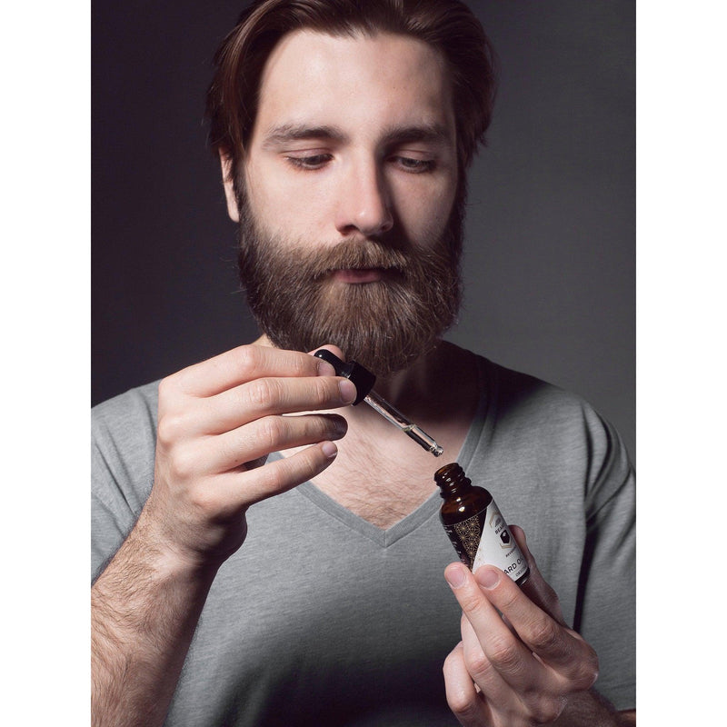 Dark haired bearded man demonstrating how to use a beard oil dropper