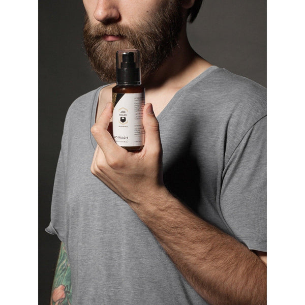 Bearded man presenting a bottle of Beard Reverence Beard Wash.