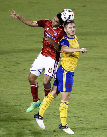 Victor Ulloa and Colorado Rapids forward Kevin Doyle, right, attempt to head the ball in the second half of an MLS soccer game in Frisco, Texas.