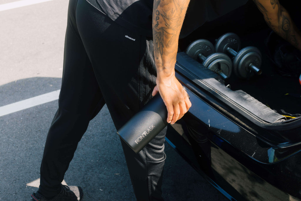 Man Holding an Iron Flask Water Bottle While Working Out