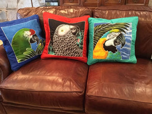 Blue & Gold macaw batik pillow cover stuffed and on a couch