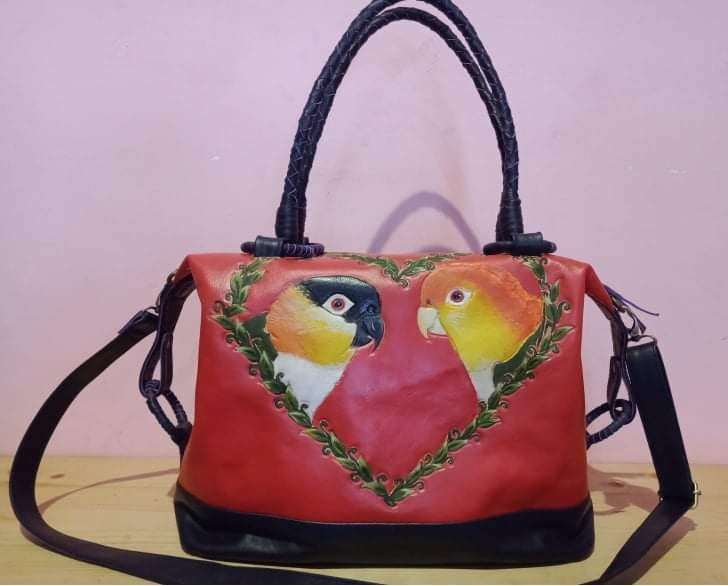 Two caiques hand-tooled and handpainted inside a heart-shaped vine on a gorgeous leather bag!