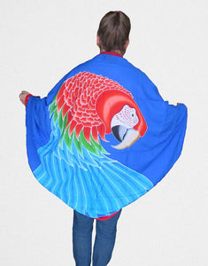 Greenwing macaw hand-painted batik sarong worn as a jacket-blue background