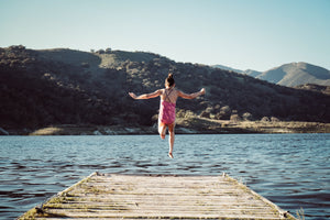 Woman jumping into fresh cold lake from wooden pier near mountains