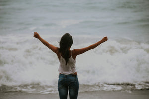 Free woman standing facing the sea with arms held out in celebration wearing white short and jeans with nice tan