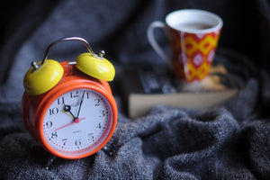 bright orange alarm clock with yellow bellow on bedside table next to patterned cup of black coffee