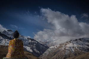 Tibetan Statue looking out over snowy mountain view and clear skies