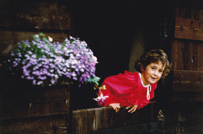 Tara Barton as child leaning over stable door smiling with hanging basket flowers and red dress